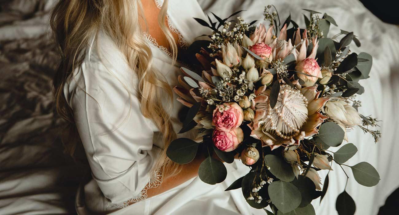 Bride holding wedding bouquet arrangement by Parksville florist Petal and Kettle