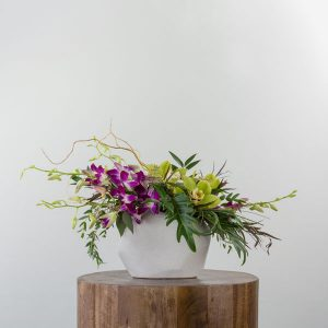 Flower arrangement by Parksville florist Petal and Kettle, yellow and purple tropical flowers and orchids